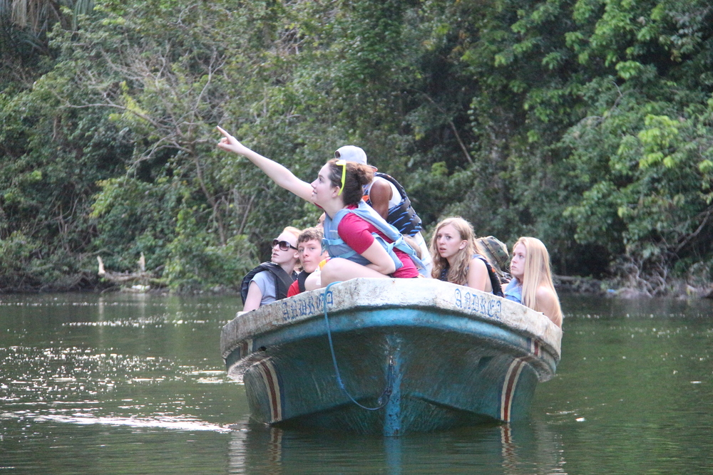 Sophomore Kelly Baillie points out a monkey hanging in the trees during a boat tour along the river leading up to the cabin.