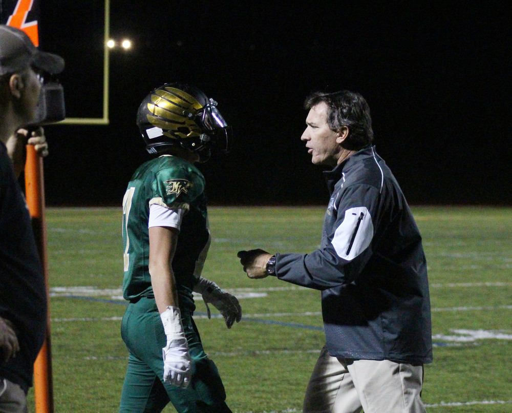 Coach Ric Cash talks to senior Kyler Mills on the sideline. Published September 2015, Vista Now