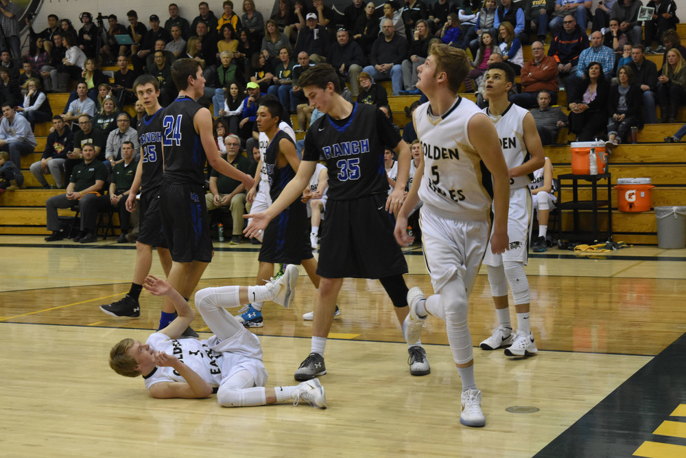 Junior Jake Belknapp watches as his lay up goes through the net while senior Trey Boeyink lays on the floor after a defensive foul on Highlands Ranch. Published February 2016, Vista Now