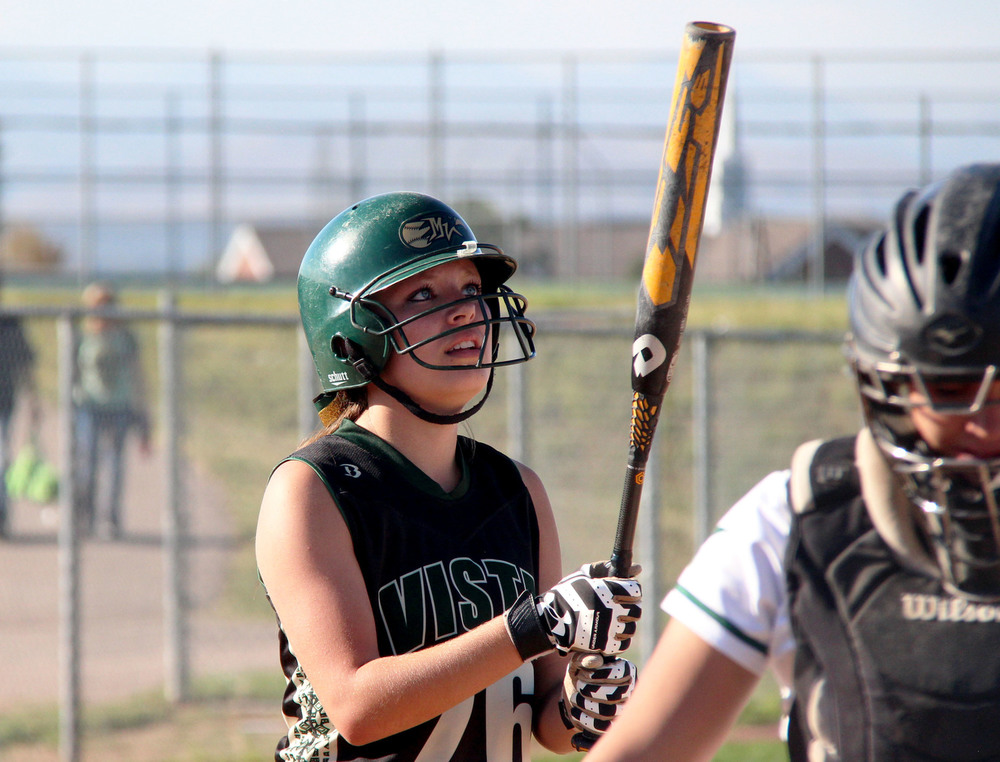 Junior Hayden Smith looks up at her bat moments before stepping into the batter's box during a rivalry game against ThunderRidge High School. Published October 2014, Vista Now