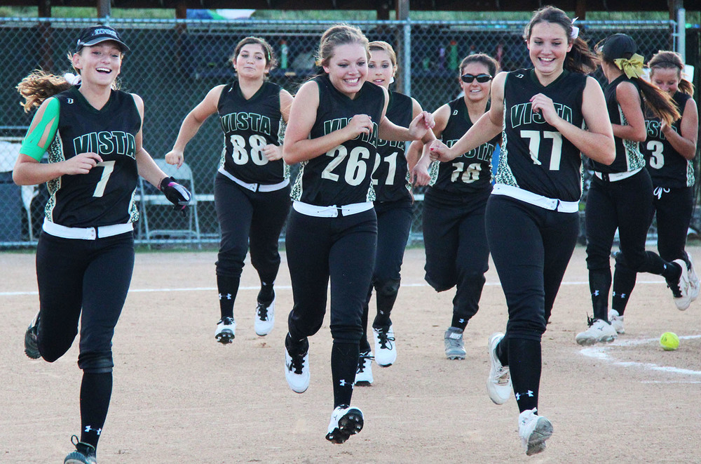 Senior Dani Klatt (left), junior Hayden Smith (middle) and senior Sarah Lang (right) celebrate with their team after defeating ThunderRidge High School, 8-7, in extra innings.Published October 2014, Vista Now