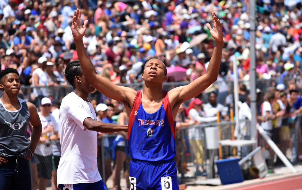 Junior Donovan Williams celebrates his team's victory in the 200 meter dash.  Published May 2016, Colorado Community Media