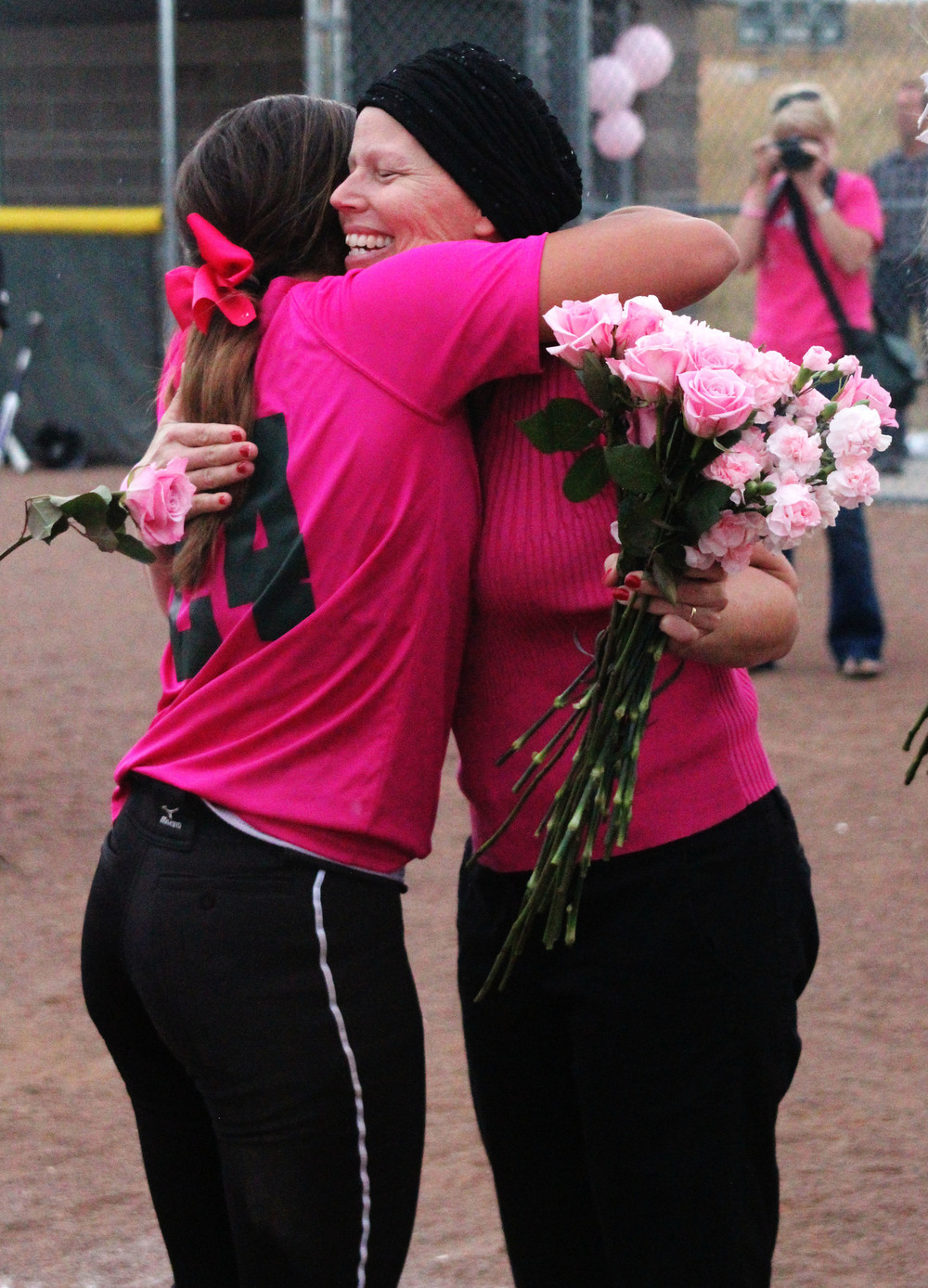 Susan Cash embraces senior Kayla Lewis during the annual softball Pink Game. Cash was diagnosed with stage 3 breast cancer earlier in the year and, after a series of remissions and complications, passed away in July of 2016. Published October 2015, Vista Now