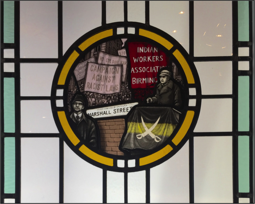 A stained glass window made by artist Steven Cartwright for the Red Lion pub, portraying a march of the Indian Workers Association (IWA). In the left foreground is Malcolm X, who was invited to the Black Country by the IWA in the 1960s.