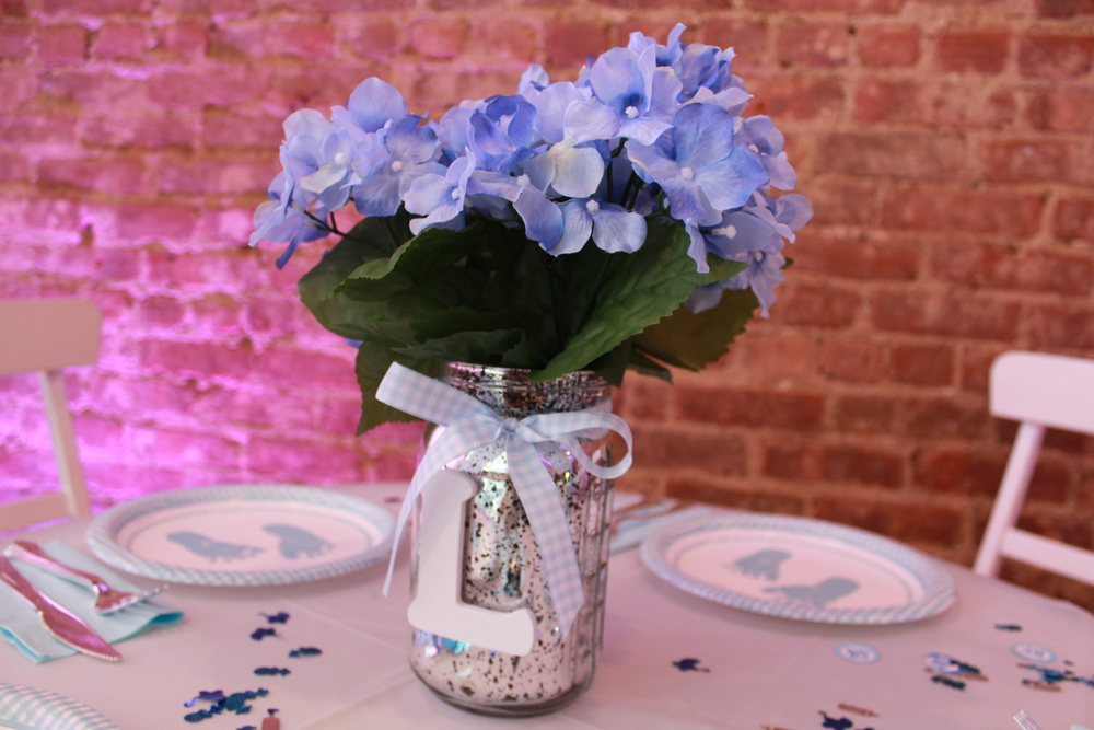 centerpieces: these silver tainted mason jars were shipped from my homeland, Dominican Republic, and i bowed it with a checkerboard ribbon along with white wooden L's for Landon. the faux blue hydrangea flowers were bought, cut, and fluffed from a local craft store.
