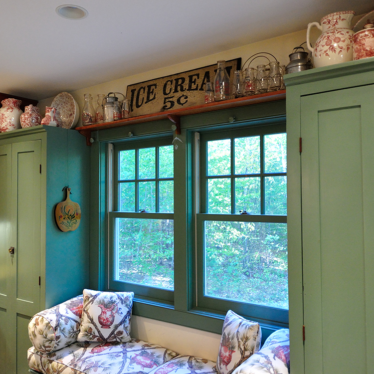 Window seat alcove framed by antique cupboards