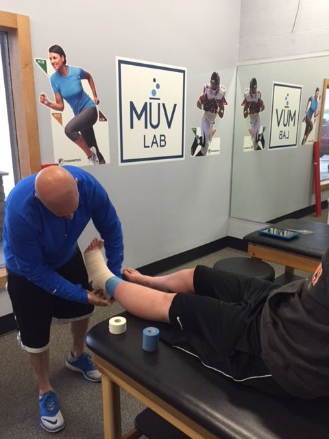 Athletic Training Services at MuvLab-DTC. Erik Phillips taping an injured ankle.