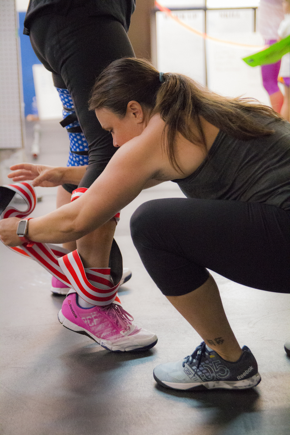 The woman's knee wrap came undone while she was squatting. A fellow competitor quickly unraveled it so she could continue with the WOD.      ~~~~LOVED this moment here~~~~  Athletes from    Elite Progression    in Mahopac, New York.