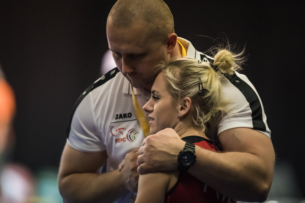 I can't remember exactly what happened here.  Notice his arms and the hand holding.  I love how his massive arms embraces the athlete.  Such a strong and intimidating looking man who displayed genuine care for his weightlifter.