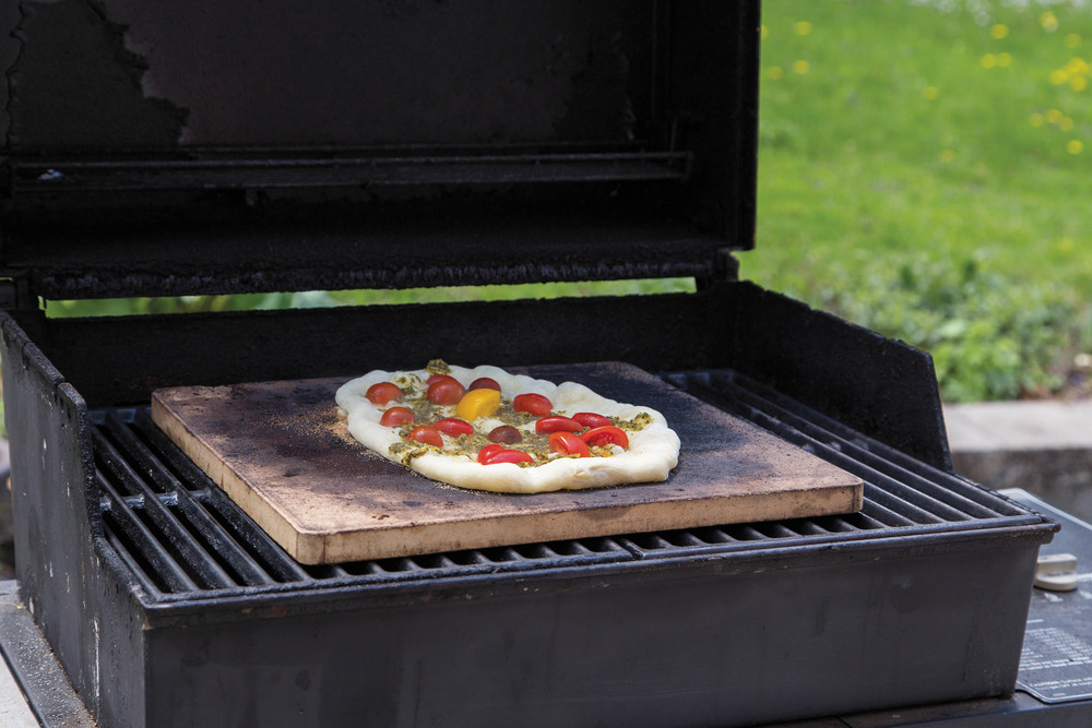 Love the idea of a wood-fired oven but your time or budget makes it unlikely that you can build your own? While the results aren't identical––and the cooking method lacks some of the romance of an earthen structure––you can use a gas or charcoal grill to approximate the results of a cob oven.    Build a fire in your grill:  Aim for medium-low to medium-high, depending on what you're cooking. Lay a baking stone on the grate and let it heat for at least half an hour. Follow your recipe, keeping the grill cover closed to approximate the oven effect of a woodfired oven.