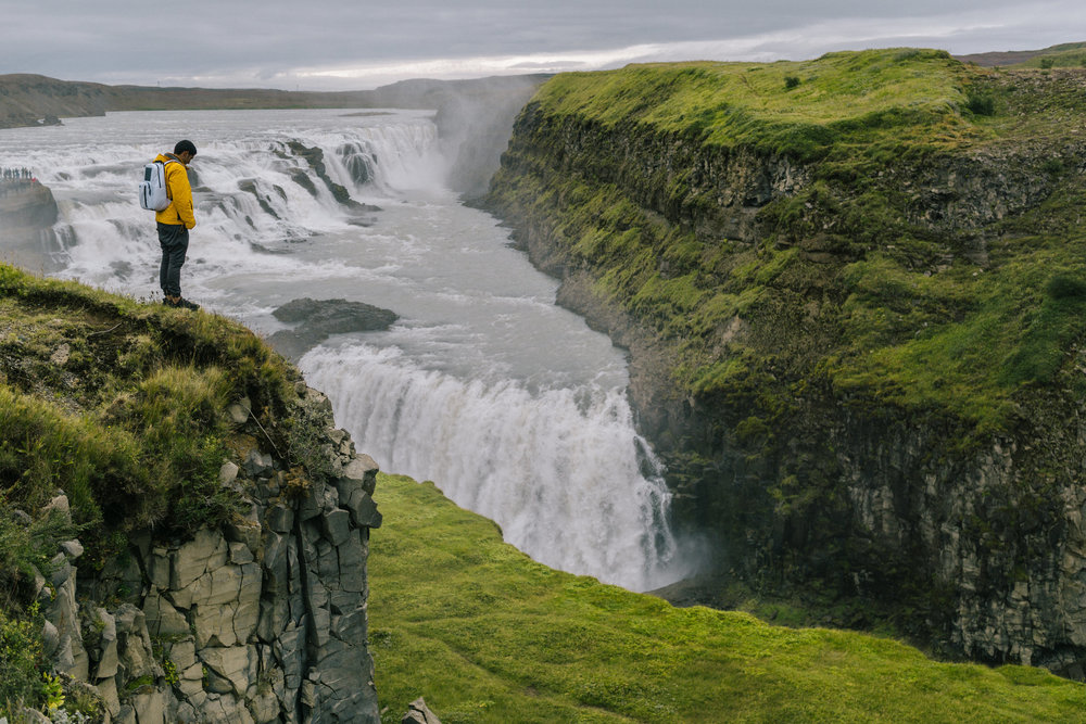 Don Henson Photography standing on a waterfall in Iceland