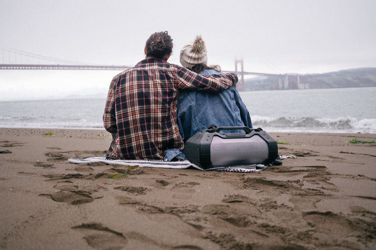 Couple listening to music on the beach on a grey cloudy day in the Pacific Northwest