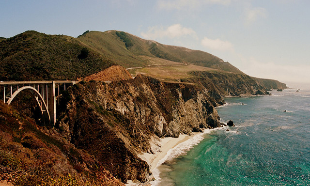"Watch the waves crash in front of the Brixby Bridge in Big Sur as you gaze longingly in your lover's eyes ""click goes the camera."""