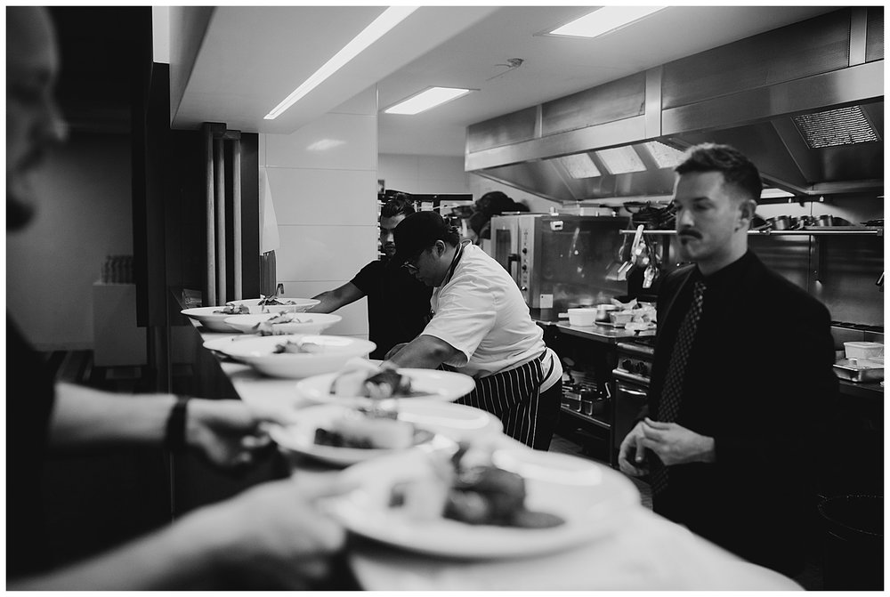 Fresh Catering prepares main courses in the kitchen at MCA during a Sydney wedding reception.