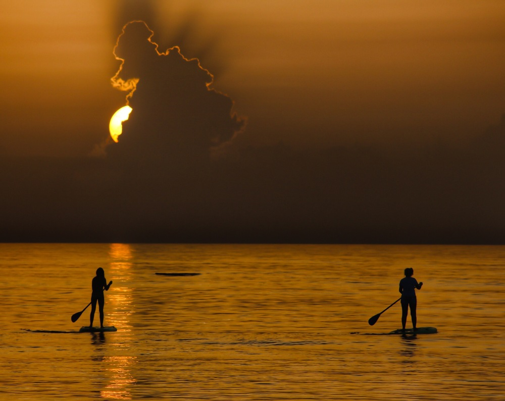 Two Stand Up Paddle Boarders head off for the horizon. Now that is the start to a day!
