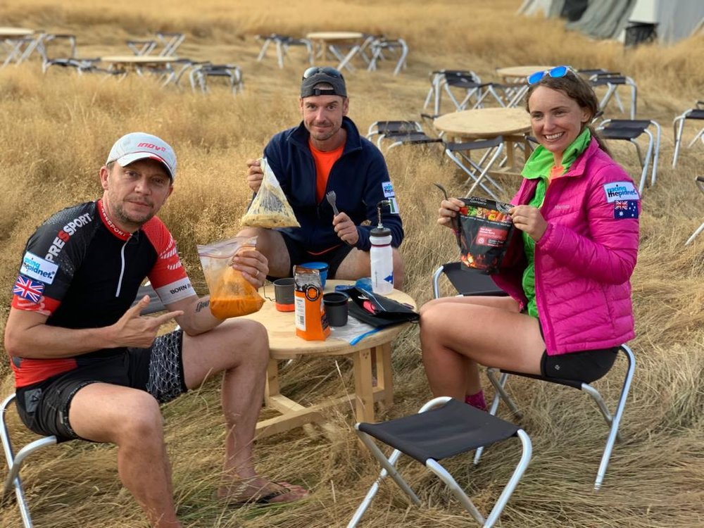 "A typical day's menu - Breakfast: 500 cals 2 x Gu Stroopwafel biscuits, with 1 big spoon of peanut butter in between. 1 x Hammer Perpetuem drink (protein and carbs) plus coffee. Some people had ramen noodles and I was insanely jealous of them by day 3.While out running/walking: 800-1000 cals 1 x Energy gel every 60 mins plus an electrolyte capsule. Snack on a Clif bar along the way. I also had some Clif blocks to chew on as extra. Aim for about 100 cals per hour. Lots of water. We had water re-fills every 10km and we had to carry 1.5L on us at all times (more weight!!).Finish: 250 cals Tailwind chocolate recovery shakeDinner: 880 cals A dehydrated meal – 2 person size. I loved The Gourmet Food Company meals – they are the fancy brand from Back Country. They were totally worth the extra cash. They even had little extra sachets to add – my lamb and mushroom risotto came with parmesan cheese.Dessert: 250 cals A spoonful of peanut butter. Seriously. I took a whole jar and it was a great snack (but a heavy one). I earned the nickname ""Peanut"" early on.Keep in mind that you burn way more than this on a day out there - so you're in calorie-deficit the whole time"