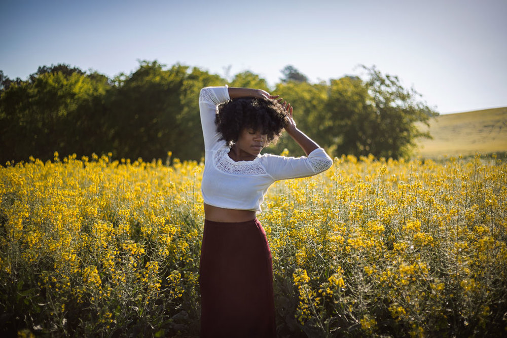Black-woman-with-afro-dancing-in-field-of-yellow-flowers-self-portrait-by-Atlanta-photographer-Chanel-French