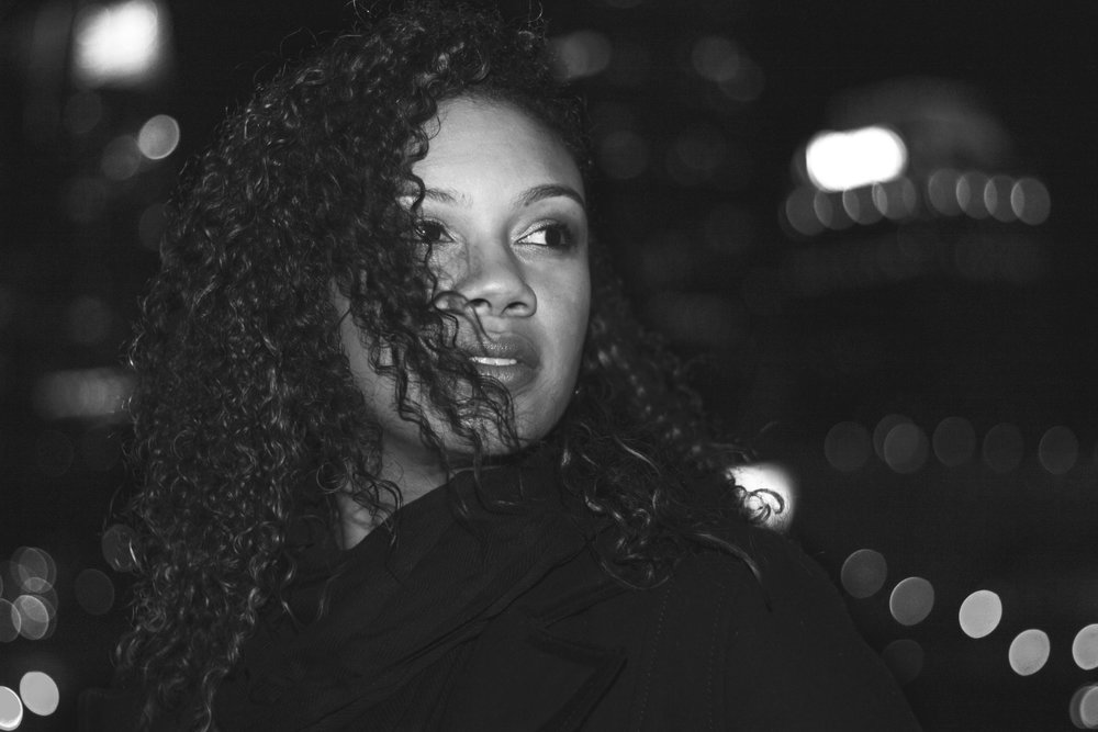 Black-and-white-photo-of-young-woman-with-curly-hair-in-downtown-Atlanta-at-night-by-photographer-Chanel-French