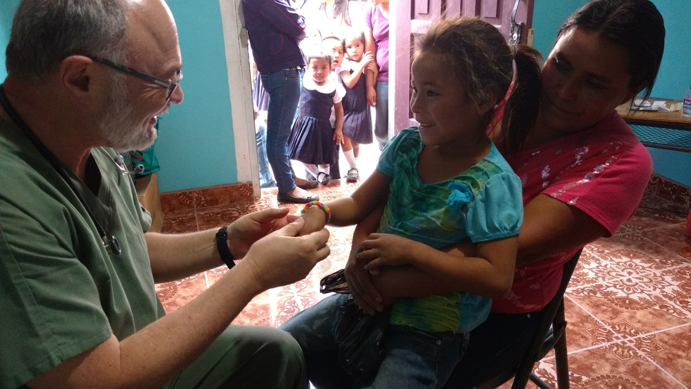Dr. Gorodzinsky gives this young patient one of the bracelets made by Nellie and Julianne.