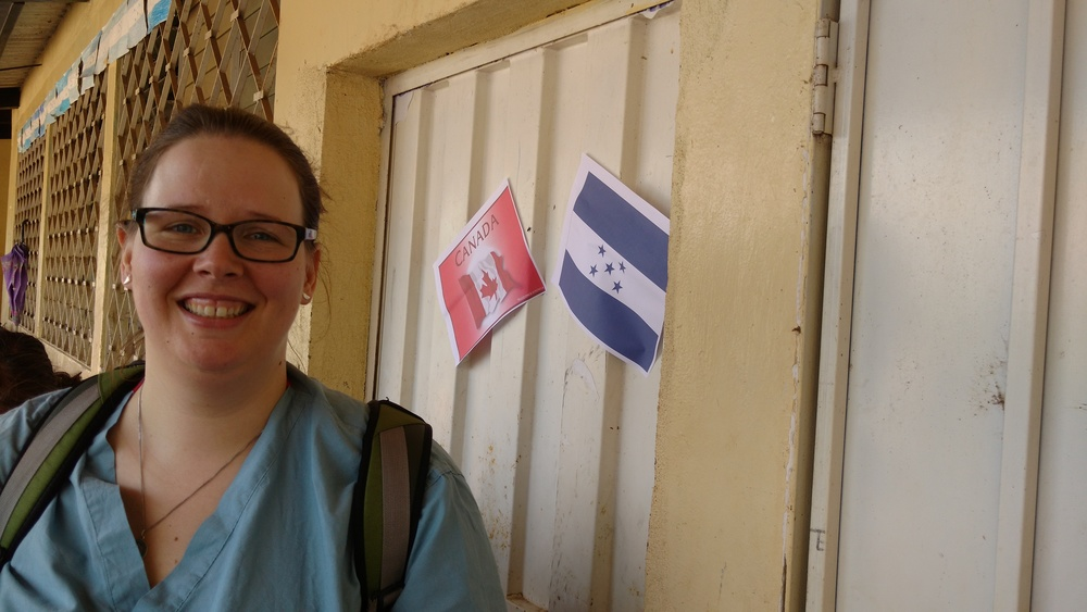 Heather standing beside our clinic room in Las Peñas, where a Canadian and Honduran flag have been placed beside each other.