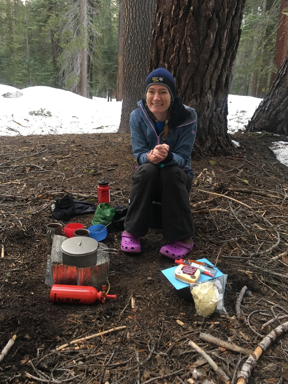 Chilly! Cheri contemplates the cooking area at our campsite before caving in and grabbing her giant down jacket.
