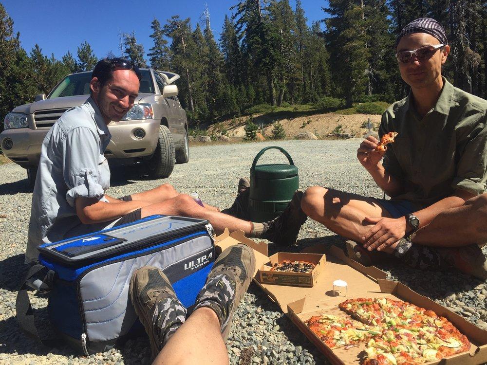 Everyone (Pitbull, Huckleberry's feet, Macro) enjoying the veggie pie on a thru-hiker table aka the ground.