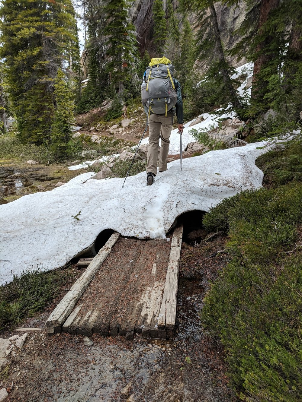 Andrew crossing a snow bridge over a wooden bridge over the soppy ground at the edges of Imogene Lake's marshy inlet