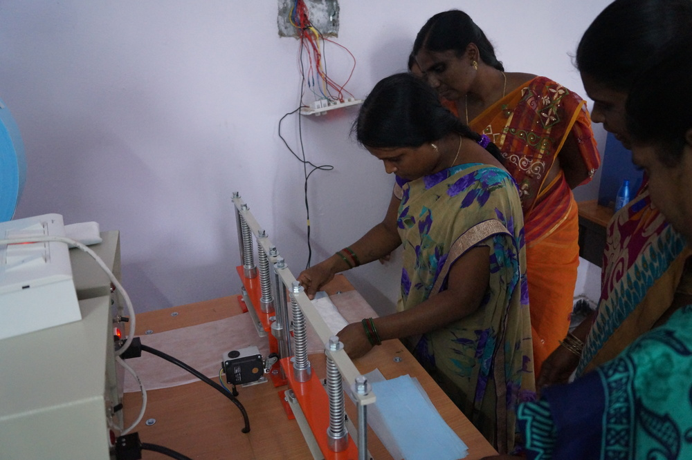 Teachers being trained to operate the sanitary pad-making machine