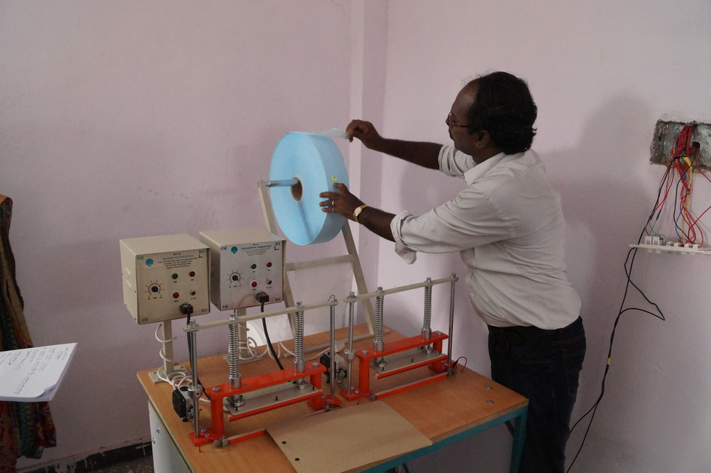 A trainer instructs participants about the mechanics of the sanitary pad-making machine
