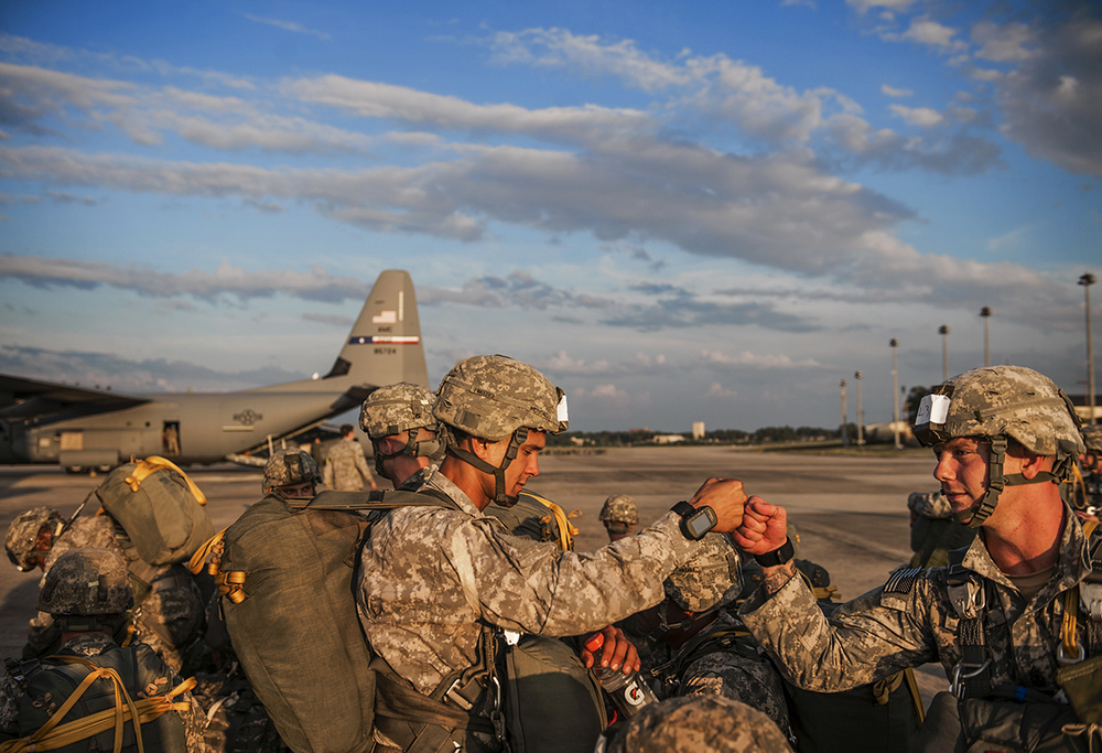 Soldiers of the 82nd Airborne Division bump fists as they prepare for take off during the Emergency Deployment Readiness Exercise on Wednesday, July 15, 2014 at Pope Airfield on Fort Bragg in Fayetteville, N.C. The soldiers have 60 hours before taking flight and parachuting into a training mission at Eglin Air Force Base in Florida. The exercise gives soldiers a chance to hone their skills in case they are needed to jump into a hostile environment or to help provide humanitarian relief.