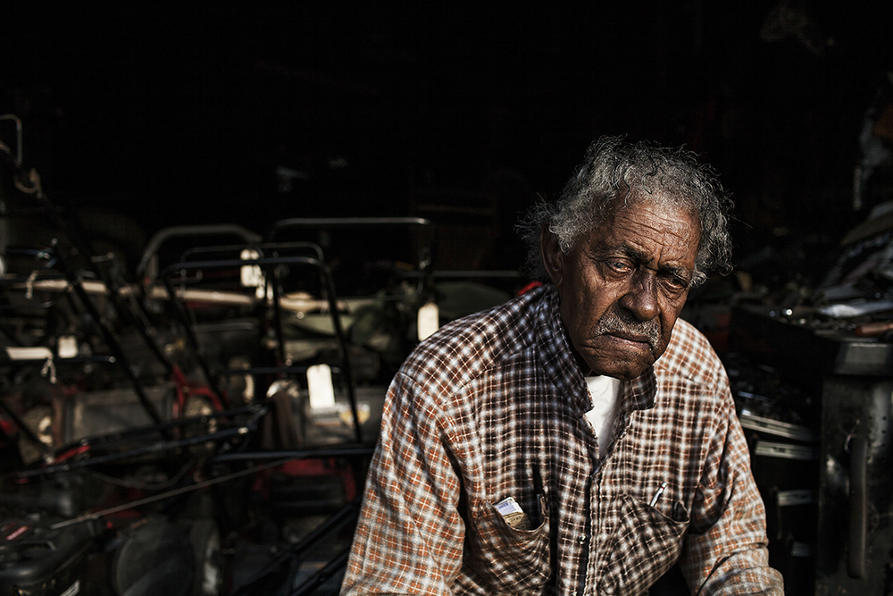 John Daye peers out from his garage where he repairs lawnmowers in Durham, N.C., on August 24, 2014. Daye has been repairing and selling lawnmowers for 21 years since his retirement as an engineer in the tobacco industry. Durham is home to the American Tobacco Company started by J.B. Duke in 1890 that soon became one of the 12 original members of the Dow Jones Industrial Average. The company left Durham in the late 1980's leaving 1,000 people without jobs.