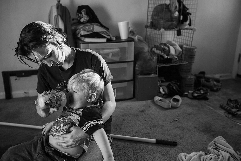 Arielle Morgan comforts her son Dominique, 2, with a sippy cup after he fell while playing in the living room in Durham, N.C. on October 15, 2015. Morgan lives with her mother as they both raise there two eight year old daughters and her son together as single mothers.  According to the U.S. Census Bureau, one in four children under the age of 18 are being raised without a father and nearly half (45%) live below the poverty line. Arielle says that it would have been impossible for her to take on the responsibility of raising her daughter on her own at age 16, especially because of her daughters medical bills. Both mothers believe that staying together and raising their children together has transformed their relationship from mother-daughter to roommates and allowed them to handle the financial burdens of being single parents.