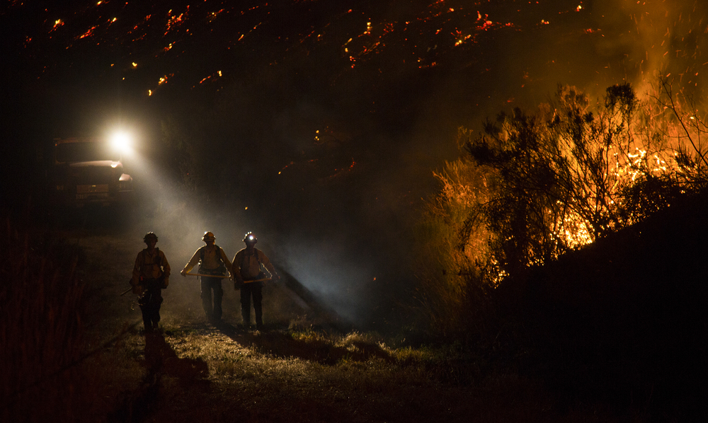 Firefighters fight the Refugio Fire along a trail behind the El Capitan Canyon camp in Santa Barbara, CA. Firefighters continue to fight more aggressive wildfires as the drought continues in California for its fifth year.