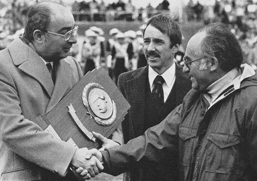 Coach Cy Fritz (right) and Assistant Coach Jeff Bradley (center) accepting the NCAA DII National Championship cross country trophy from MU President Joseph Caputo in 1981