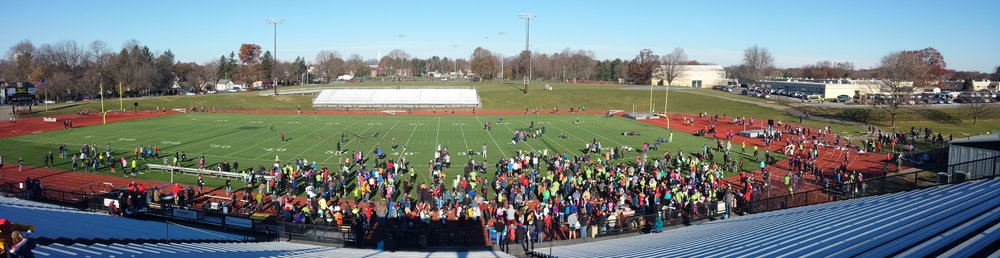 A crowd gathers as runners finish the race inside Biemesderfer Stadium on the campus of Millersville University