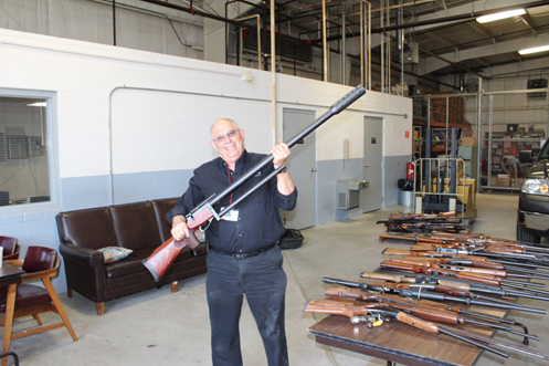 Steve Chafitz, e-End's President, is shown with a 50 caliber sniper rifle before it was destroyed