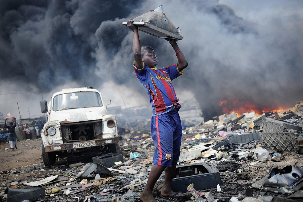 Tires burn in the background as a boy at the world's largest e-dump in Ghana repeatedly smashes a TV into the ground to break it open. Photo: Kai Löffelbein