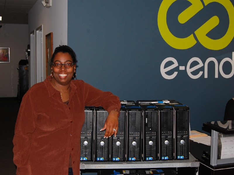 Mrs. Sheri Green, executive director of MI Foundation, standing with donated computer towers she received from e-End in November 2017.
