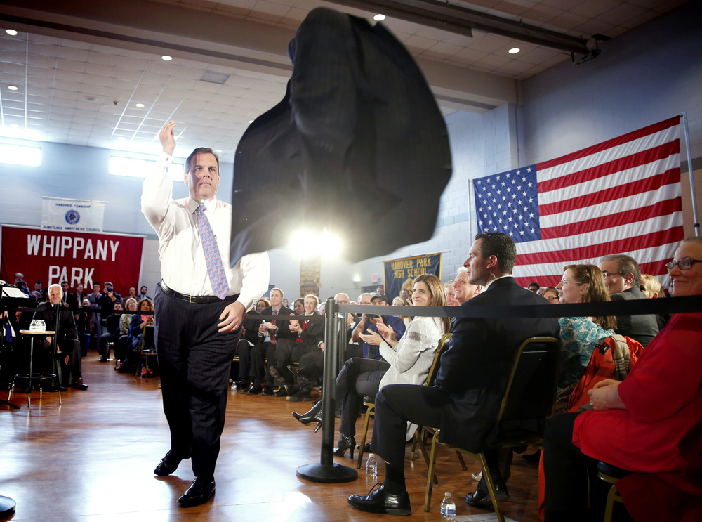 JACKET TOSS - Just prior to answer questions, Gov. Christie continues the tradition of taking off his jacket and throwing it to one of his aides. NJ Governor Chris Christie holds his 132nd Town Hall Meeting In Whippany at the Hanover Township Community Center.  Tuesday March 24, 2015. Whippany, NJ, USA