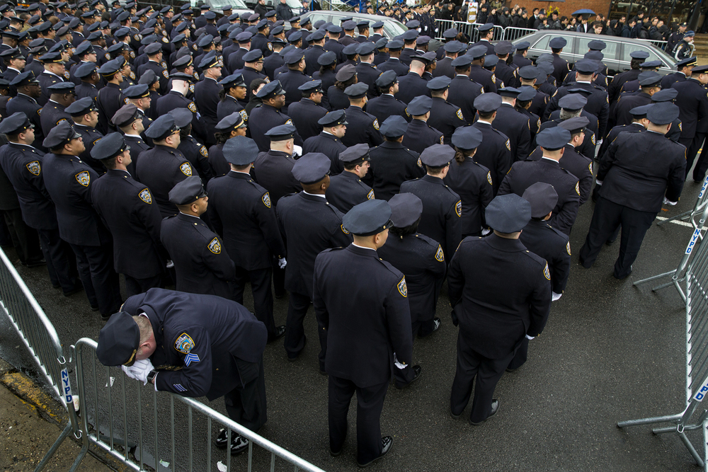 A police officer from a squad with the 84th Precinct rests his head on a barricade during services Sunday, Jan. 4, 2015, outside the funeral for NYPD Det. Wenjian Liu, one of two officers slain Dec. 20, 2014, as they sat in a patrol car in Brooklyn. The gunman took his own life shortly thereafter on a nearby subway platform.