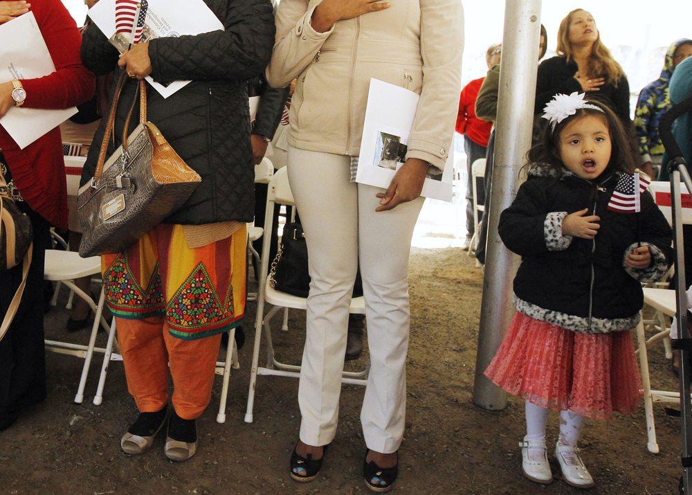 Four-year-old Camila Polanco, right,  stands with some of the 34 new citizens naturalized during ceremonies held at Paterson Great Falls National Park. Her mother Mary Polanco was one of the people who became a U.S. citizen today.  Paterson, NJ  12/10/2015