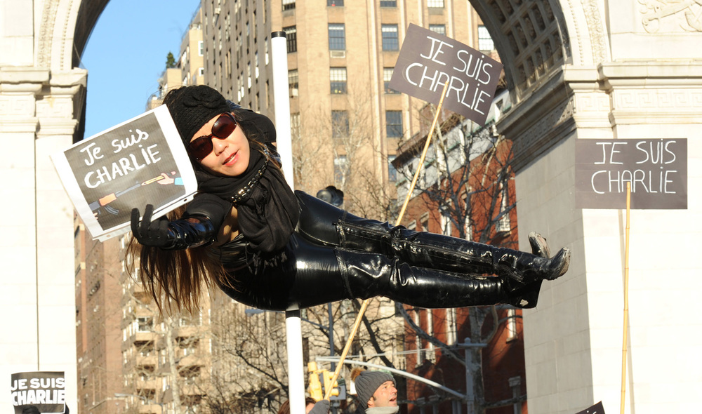 "January 10, 2015 - New York, United States:  Charlie Hebdo supporters held a vigil in Washington Square Park near New York University to show their respect and solidarity for those murdered and free speech.  ""Je Suis Charlie"" placards dotted the crowd throughout the crowd.  Carolyn Chiu (above), Yoga Pole Instructor, showed her support."