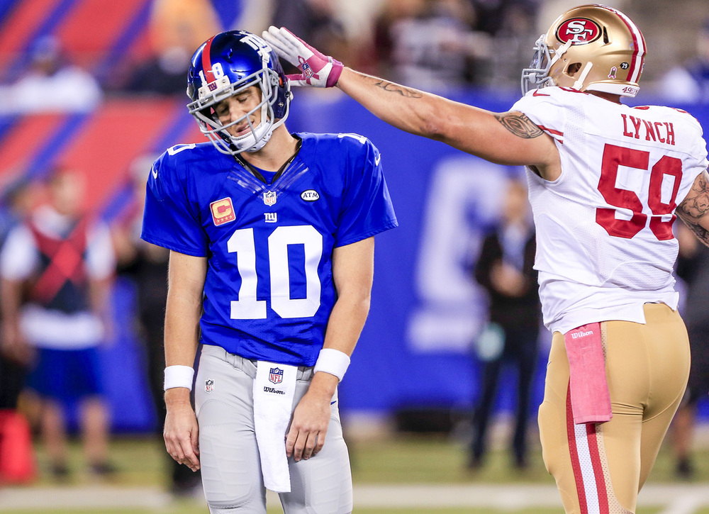 EAST RUTHERFORD, NJ — Oct. 11, 2015 — New York Giants quarterback Eli Manning (10, left) gets a tap on the helmet by San Francisco 49ers outside linebacker Aaron Lynch (59) after Manning threw an interception in the end zone late in the second quarter as the Giants host the 49ers in NFL Week 5 action Sunday night at MetLife Stadium.