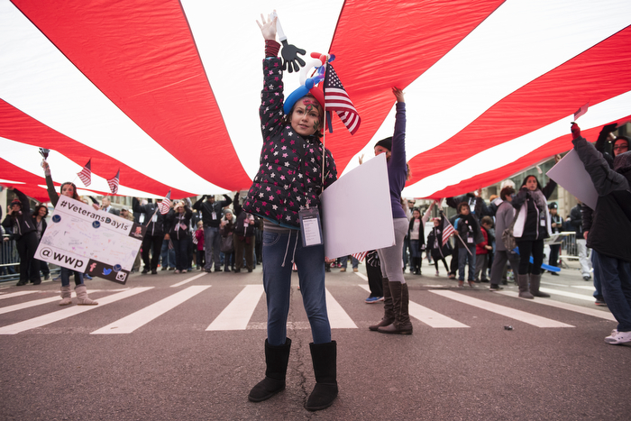 Children go underneath a big American flag of Veterans Day Parade NYC on Wednesday November 11, 2015 in Manhattan