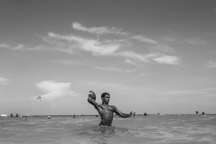 Eighth grader Josh McKenzie throws a football while swimming at the beach at South Beach, Miami a day before he plays in a showcase All American football game at Florida International University's Biscayne Campus.