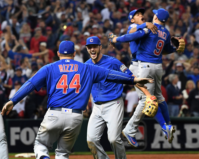 Chicago Cubs third basemen Kris Bryant celebrates with first baseman Anthony Rizzo after his throw retired Cleveland Indians Michael Martinez for the final out in the 10th inning of game 7 of the World Series in Cleveland, Ohio in the early morning of November 3, 2016. In the background, Cubs shortstop Addison Russell leaps into the arms of second baseman Javier Baez.  Bryant was the World Series MVP and Chicago won 8-7 to celebrate their first World Series championship in 108 years.