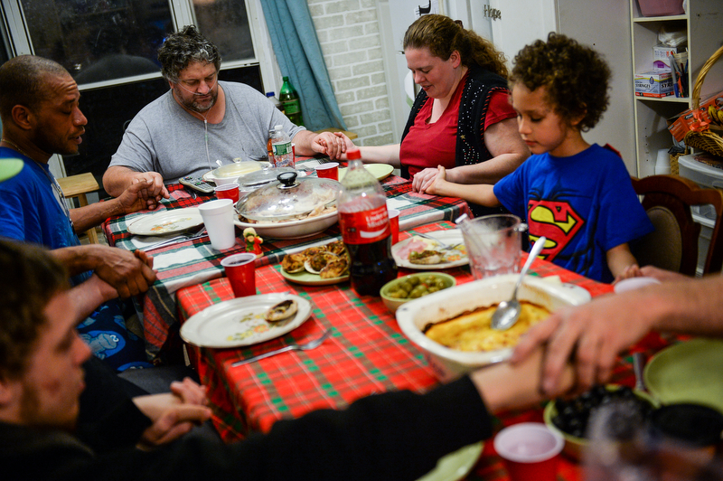 Dawn, her family, and Bob, center, hold hands while saying a prayer over Christmas dinner inside Bob's trailer. By combining the money they receive from state aid the two families are in search of a home in upstate New York before their eviction date.