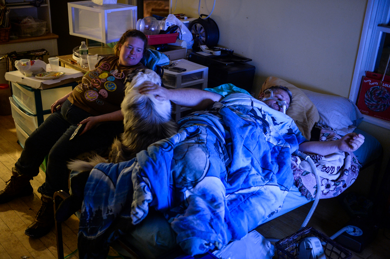 Bob, with CPAP mask on, lays on a small bed fixed up by Dawn in her trailer for the night. In the last week they were able to find a rental home in Schenevus, New York. With the board up company arriving in the morning the two families will head upstate tomorrow.