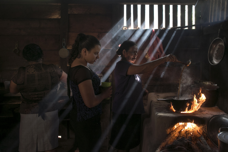 January 06, 2016 - Rodeo Grande, Nicaragua: Amada Garcia, right, brews coffee with beans grown by her family as her sister Pastors Hernandez,left, prepares food and Ms. Garcia's daughter-in-law Lucy Calderon, center, looks on in their kitchen in Rodeo Grande, a small village near Esteli, Jan. 06, 2016. Nicaragua, the second poorest country in the Western Hemisphere after Haiti, has been hard hit by climate change and drought but sustainable farming and irrigation projects have given some communities a means of survival.