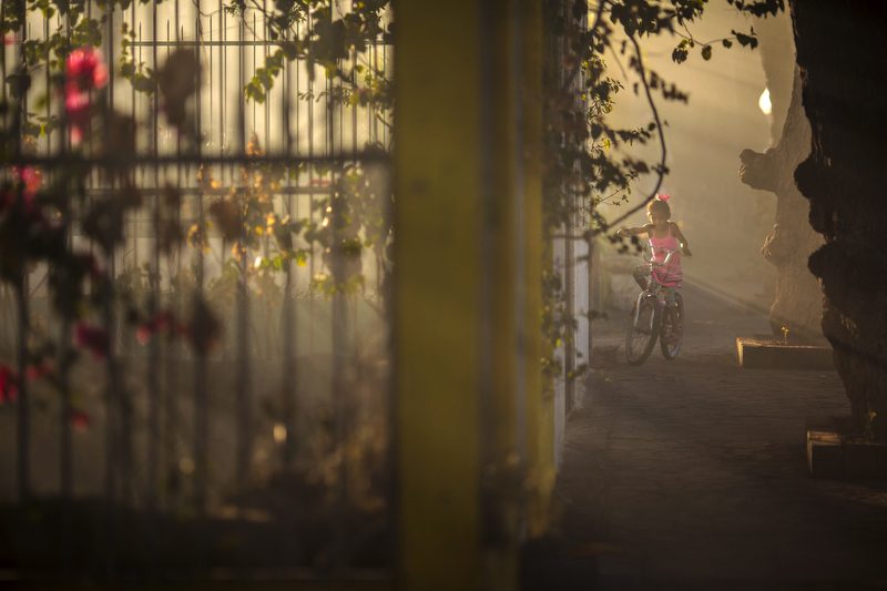 Jan. 16, 2016 - Granada, Nicaragua: A girl rides her bike through the smoke of a nearby fire, intentionally lit in a neighboring yard, near Lake Nicaragua in Granada, Jan. 16, 2016. Nicaragua, the second poorest country in the Western Hemisphere after Haiti, has been hard hit by climate change and drought but sustainable farming and irrigation projects have given some communities a means of survival.